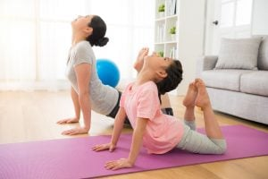 asian mother and daughter doing yoga exercises on vacation in the room at home. people having fun indoors with fitness. concept of friendly family and of summer day.