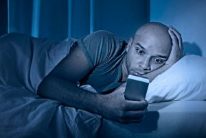 man on phone in bed | Nucific